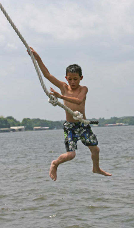 Brian K. Diggs/AMERICAN-STATESMAN Michael Kaplan swings off a rope swing into Lake LBJ. The boys and girls have separate waterfronts. They also can take out kayaks and small sailboats.