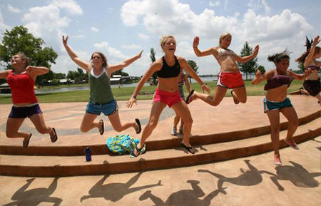 Brian K. Diggs/AMERICAN-STATESMAN Allison Lewis, left, Molly Reidy, Manda Martin, Brooke Strake, Lauren Parra and Jessica Grenader jump off the stage at Camp Champions. During the evening torchlight ceremony, the camp uses the stage for skits, songs and announcements. The stage is where the evening Torchlight ceremony with skits, songs and announcements takes place.